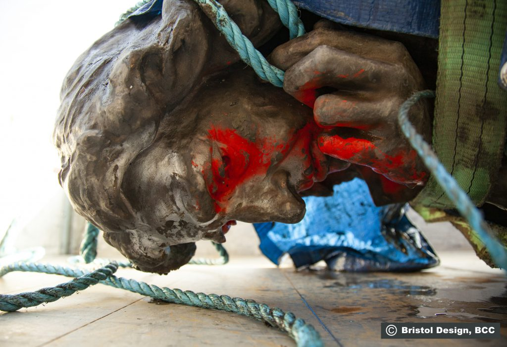 A close-up of the statue's head after being recovered from the harbor. Red spray paint has been applied to the eyes, mouth, and right hand.